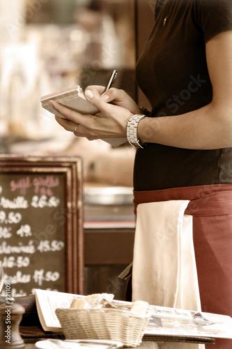 Stonowanych na zewnątrz kawiarni sceny z kelnerka podejmowania porządku
