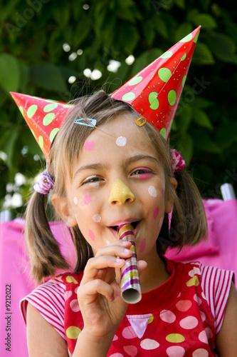 petit clown soufflant des balles en riant