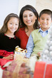 Mother With Her Son And Daughter Holding Christmas Gifts