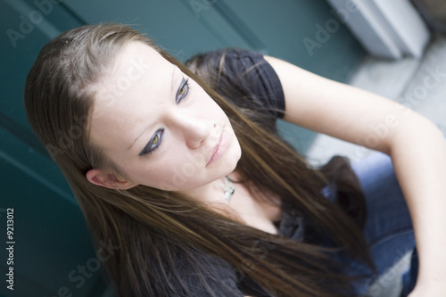 Young woman sitting on a doorstep in thought