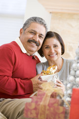 Middle Aged Couple Sitting On Sofa Holding Christmas Present