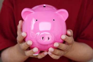 Boy Holding Piggy Bank With His Savings