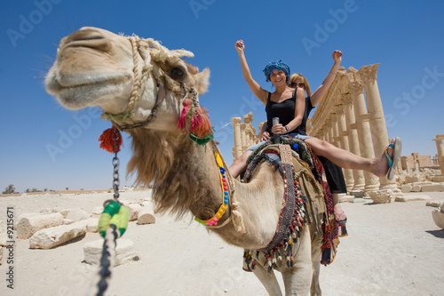 two girls are ride on camel in desert - 9215671