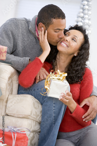 Husband And Wife Affectionately Exchanging Christmas Gifts