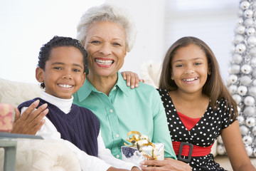 Grandmother Sitting With Her Two Grandchildren,Holding A Christm