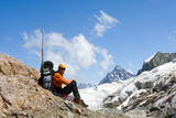 Man with backpack sitting on rock in high mountains poster