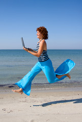 Girl with laptop running along sea coast
