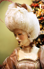 Beautiful doll on a background of a New Year tree