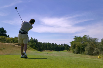 Shot of a male golfer teeing off with the ball in mid air