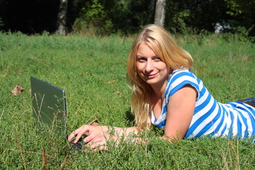 Frau im Park mit Laptop