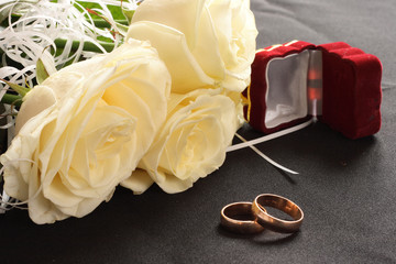 wedding rings, box and white roses on black background