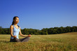 Girl practicing yoga in a summer meadow.