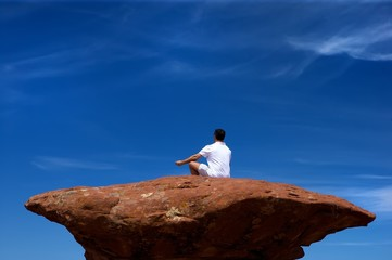 An image of a man meditating on a high rock formation