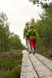 Mother and daughter walking on  plank-way in forest poster