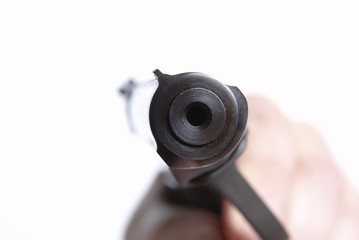 The pistol directed on you, on a white background, shallow DOF