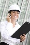 Woman wearing hardhat using mobile phone poster