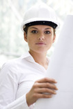 Woman wearing a hardhat holding blueprints poster