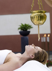 Frau jung im Spa mit Öl gießen auf Stirn,