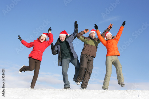 Friends with Santa hats dance on flank of hill