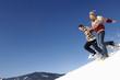 Junges Paar im Schnee, bergab laufen