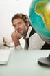 Junger Mann sitzen am Schreibtisch, Globus im Vordergrund