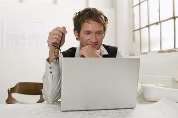 Junger Mann arbeiten am Laptop