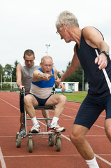 Disabled person and his helper reaching for an other athlete .