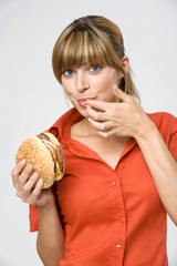 Frau jung Finger lecken, halten hamburger, Portrait, close-up