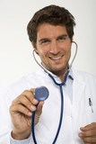 Male doctor holding stethoscope, close-up, portrait