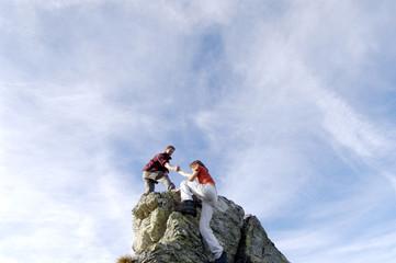 Junges Paar klettern auf Gipfel, Mann hilft Frau,