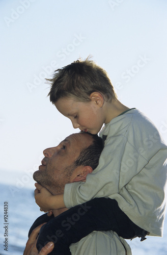 Father carrying son (4-7) on shoulders, close-up