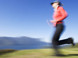 Young woman jogging, side view, (blurred motion)