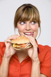 Young woman holding hamburger, licking lips, close-up