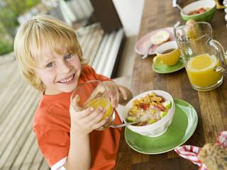 Junge am Frühstückstisch, halten Glas Saft