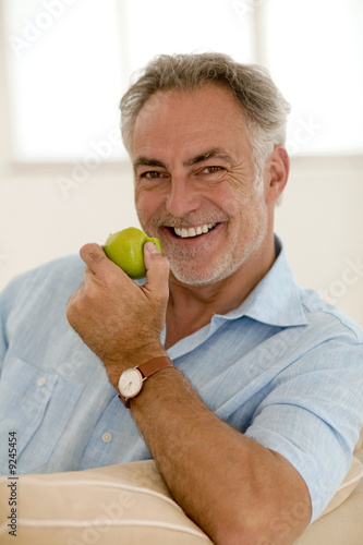 Mature man sitting on sofa holding apple, smiling, portrait