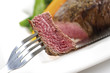 Piece of beef filet on fork, elevated view