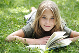 Girl (13-14) lying on grass reading, smiling