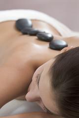 Frau jung bekommen Massage mit heißen Steinen, close-up