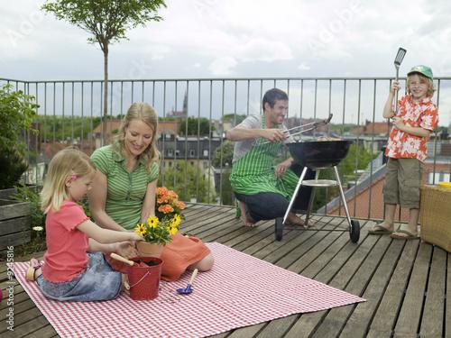 Familie auf dem Balkon, der Vater, der Grill vorbereiten