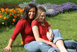 beautiful barefoot mother and daughter sitting on the grass poster