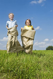 Boy and girl sack racing