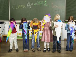 Kinder stehen vor der Tafel, Blick in die Schultüte