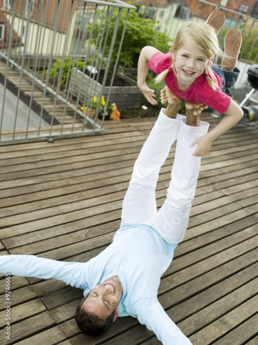 Father balancing daughter on feet