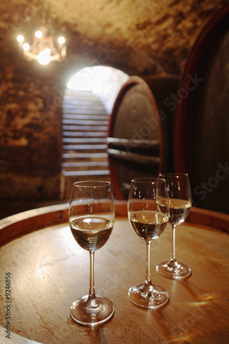 White wine in glasses on wine cask, close-up