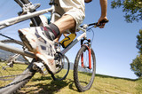 Young man riding mountain bike, low angle view, low section
