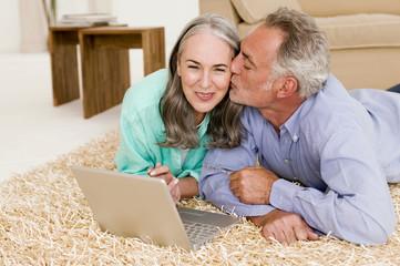 Junges Paar liegen auf dem Teppich mit Laptop, Mann küssen Frau