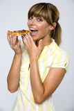 Young woman eating slice of pizza, smiling