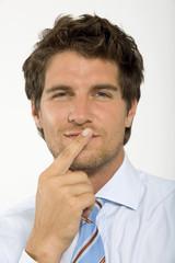 Junger Geschäftsmann mit Finger auf die Lippen, lächeln, close-up, Portrait