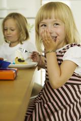 Zwei Mädchen Kuchen essen in der Küche