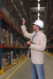 supervisor in hardhat counting stocks in warehouse poster